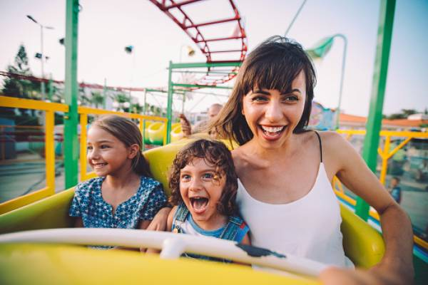 young woman and two young girls on a yellow roller coaster