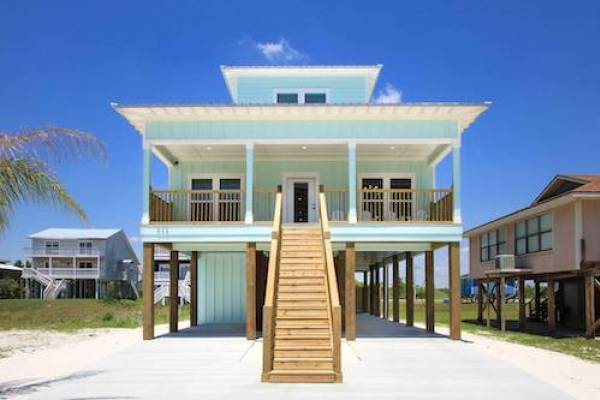 gulf shores vacation home with staircase leading up to the patio of the turquoise home on a sunny day