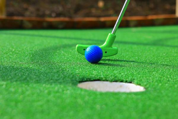lime green club and blue ball on mini golf course