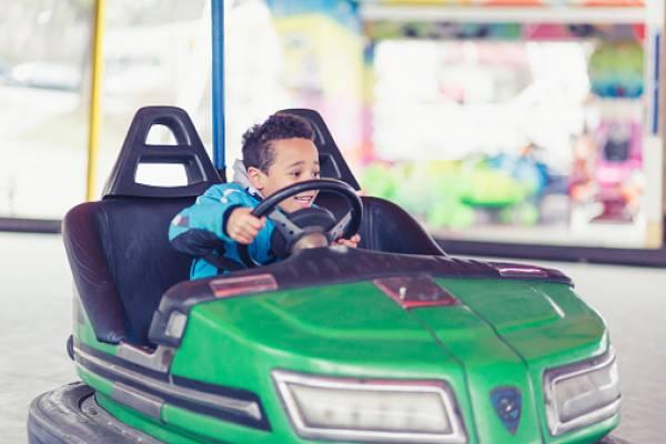 little boy in a green bumper car
