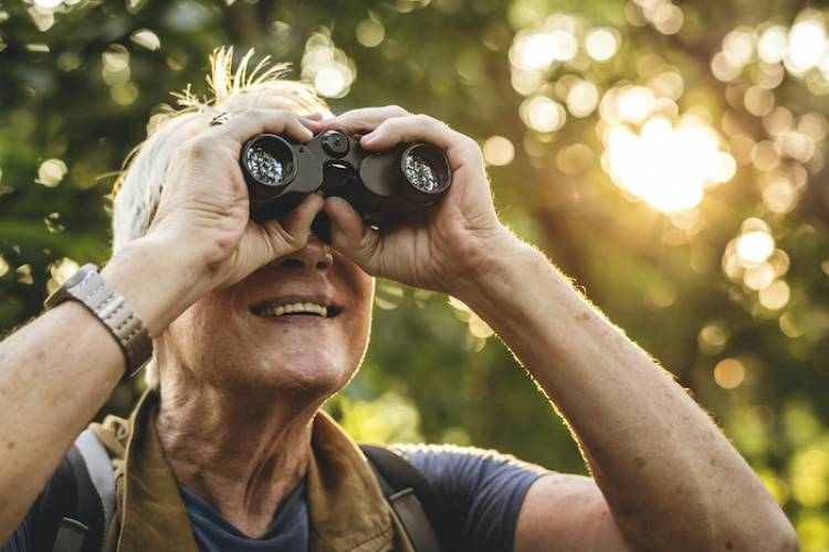 older woman with binoculars looking birdwatching in the forest