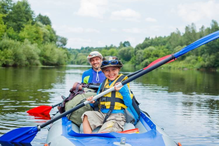 young kid and dad on a tandem kayak that is blue with blue and red ores on a river