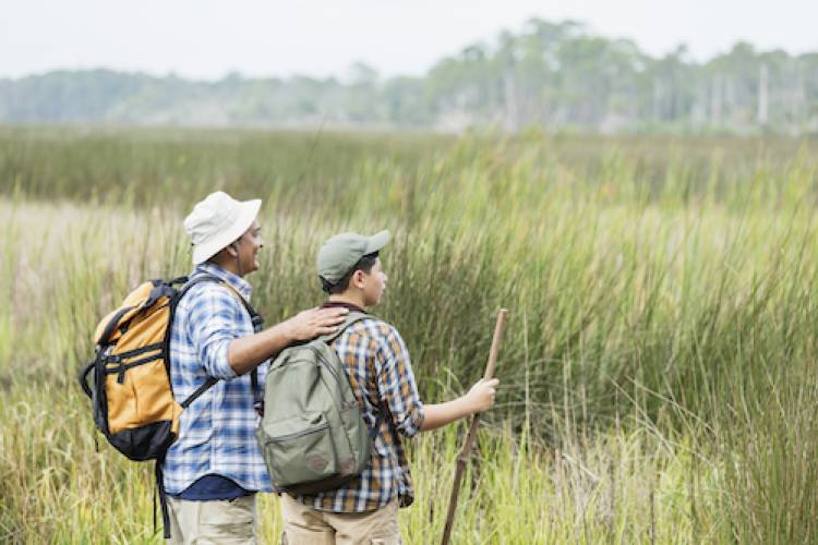 man and son hiking through the grasslands with sun hats on