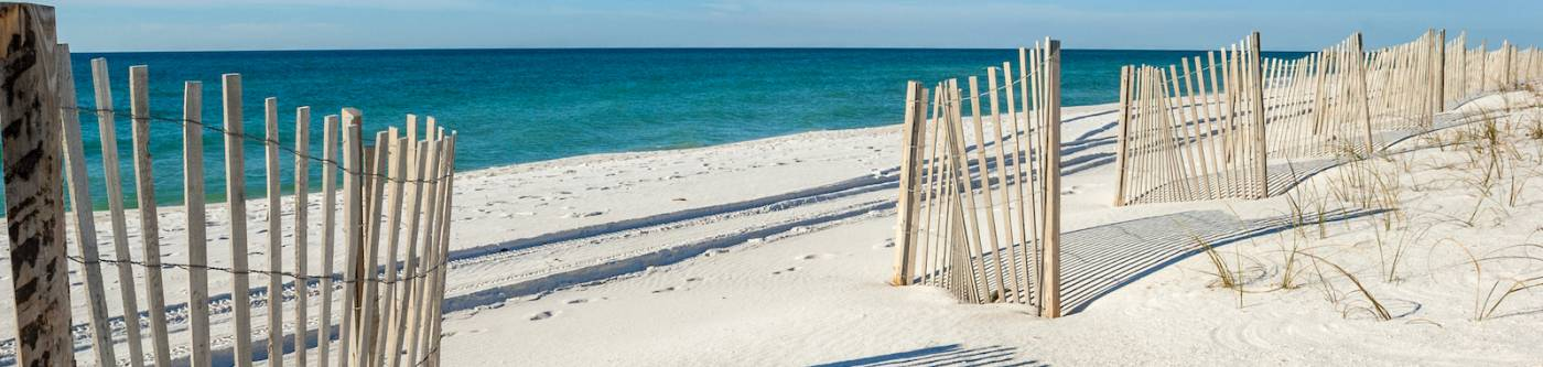 gulf shores beach alabama with fence in foreground and bright blue sky