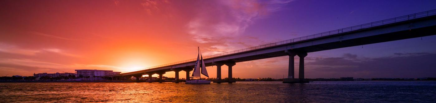 sunset along Orange Beach with a bridge in the foreground and bright blue, purple and red colors fill the sky